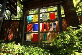 "In the front yard of Helen Rosenau's Eugene home hang several of her fused-glass artworks. Rosenau, who prefers to work in square, says this piece, Her Twelve Tribes, represents ""the world of the unseen."" (Photography by Collin Andrew/The Register-Guard)"
